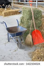 Wheelbarrow Cart Broom and Shovel in Stable at Farm