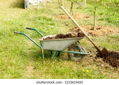 Wheelbarrow with fertilizer and shovel during the seasonal planting of agriculture .For your design