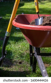 wheelbarrow filled with dirt and a trowle