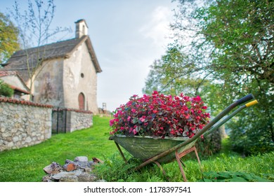 Wheelbarrow full of flowers in a village in northern Italy.
