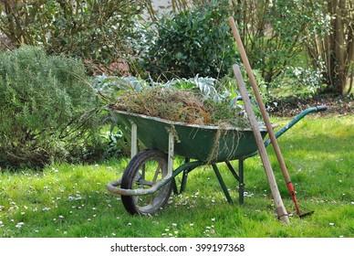 wheelbarrow full with garden weeds and tools in a garden
