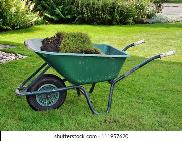 A wheelbarrow full of turf in the garden.