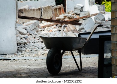 wheelbarrow on the background of demolition of a garage - construction rubble
