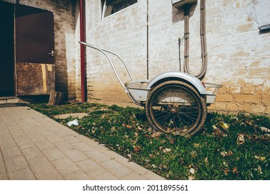 Wheelbarrow on a grass field with an interesting background of an old house . High quality photo