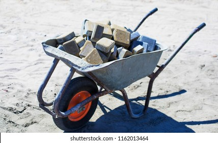 Wheelbarrow with pavement. Paving slabs. Construction of sidewalks. Building materials for the construction of the sidewalk. Metal wheelbarrow cart