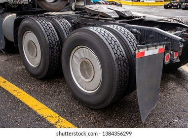 Wheelbase of industrial grade professional big rig freight transportation semi truck with two axles and twin wheels with full tread on them with mud flaps and fifth wheel for coupling of semi trailer