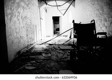 Wheelchair in an abandoned building with very low light and sunbeams through window