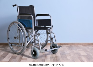 Wheelchair against color wall in room. Elderly care concept