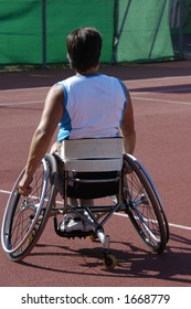 A wheelchair athlete taking a moment's pause during a tennis championship match. Her tennis racquet can just be seen in her right hand and a little sweat on the back of her blouse.