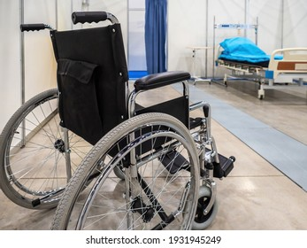 Wheelchair in a hospital ward. Wheelchair on wheels. Chair for transporting patients around hospital. Rear view of a wheelchair. Concept - sale of hospital equipment. Bed for patient in background
