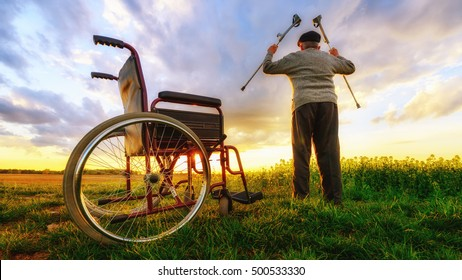 Wheelchair - miracle recovery: Old man gets up from wheelchair and raises hands up. Shot in a meadow. Recovery concept