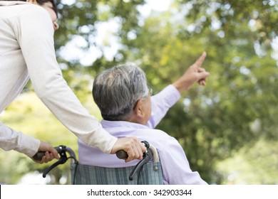 Wheelchair old man and a helper