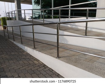 A wheelchair ramp, an inclined plane installed in addition to or instead of stairs, Slope walkway for disabled people, people pushing strollers, carts with stainless bars to prevent falling