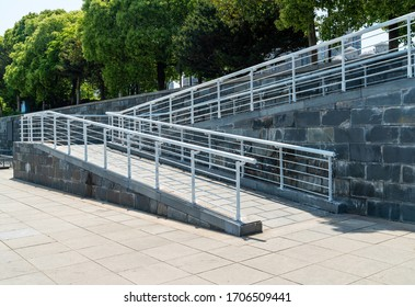 Eine Rollstuhlrampe, eine geneigte Ebene, die zusätzlich zu oder anstelle von Treppen angebracht ist, Steigungssteg für Behinderte, Personen, die die Rollen drücken, Wagen mit rostfreiem Balken, um zu verhindern, dass sie fallen
