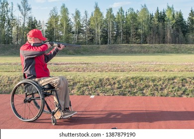 wheelchair shoots skeet on a trench stand with a shotgun man skeet shooting outdoors; shooting clay pigeon targets at gun club with airborne casing