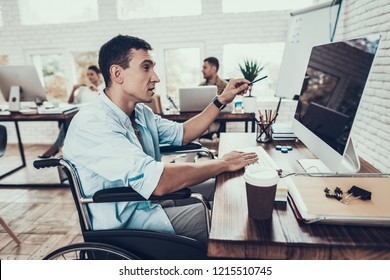 Wheelchair Working on Computer in Office. Disabled Young Man. Man on Wheelchair. Recovery and Healthcare Concepts. Teamwork in Office. Young Worker. Sitting Man. Man with Computer.
