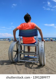 wheelchair with a young boy on the beach of the resort in summer