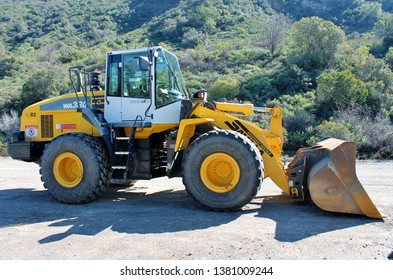 A wheeled front loader construction truck parked in a dirt lot in the foothills of California