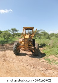Wheeled grader stands on dirt road in sacvanna. Serengeti National Park, Tanzania, Africa.