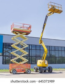 Wheeled scissor lift and wheeled articulated lift with telescoping boom and basket on an asphalt ground against the sky and an industrial building