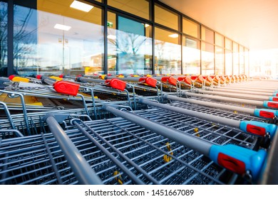 Wheeled shopping carts for customer transport and colorful shopping center shop windows, glasses in backlit, strong sunlight from the front