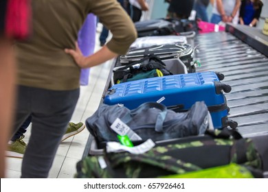 Wheeled suitcases and backpacks on a luggage belt at the airport terminal.