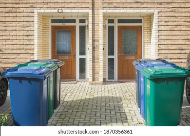 Wheelie bins outside the front doors, labelled for recycling, garden waste and refuse waste, at the Grahame Park Estate in north London