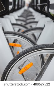 Wheels of bicycles parked at bike parking lot.Rental bicycle pickup station.Close up,shallow depth of field.Clean and safe ecological city transportation
