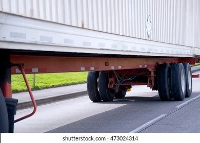 Wheels and chassis on orange frame of long commercial semi truck trailer mounted with a ribbed container for transport of dry industrial goods over long distances freights.
