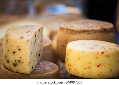 Wheels of cheese seasoned with herbs to sell on stall