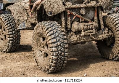 Wheels of off road car stuck full of mu