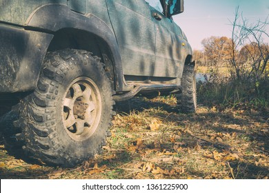 Wheels off-road car standing on the grass in the forest. Selective focus