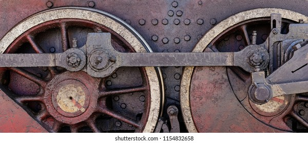 Wheels of old steam locomotive, closeup shot, industrial background