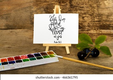 When I afraid, I put my trust in you. Inspirational and motivational quote.  Brush calligraphy. Easel, paints and blue plums Hand drawing lettering.   Words about God.