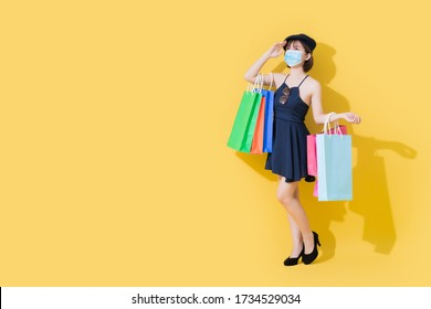 When the coronavirus crisis or covid19 improves. Cute Asian women wear blue dresses. She wears surgical masks and carrying shopping bags. She uses her hands to block the light.