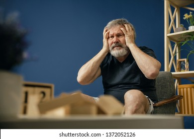 When dreams are dying. Old bearded man with alzheimer desease sitting on the chair and suffering from headache. Concept of illness, memory loss due to dementia, healthcare, depression, stress out.