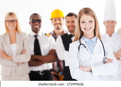 When I grow up I will be a doctor. Beautiful young female doctor keeping arms crossed and smiling while group of people in different professions standing in the background