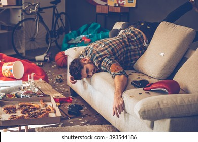 When the party is over. Young handsome man passed out on sofa in messy room after party