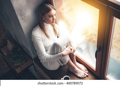 When it is rainy outside. Top view of beautiful young woman looking through window while sitting at windowsill at home