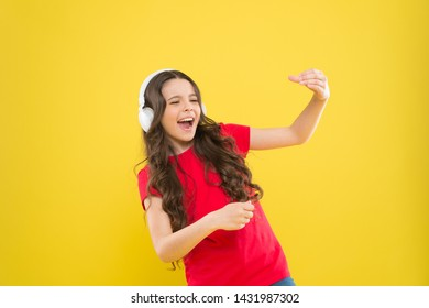When the soul is singing. Adorable small child singing on yellow background. Cute little girl listening to music in earphones and singing song. Musician enjoying solo singing.