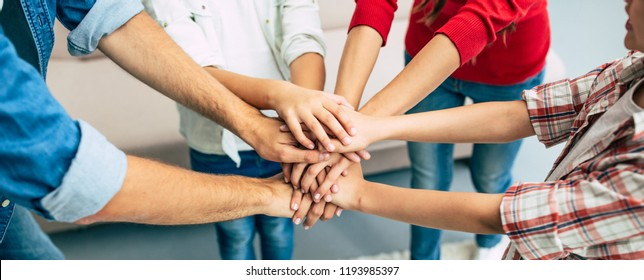 When we are together, we are stronger. Excited and happy beautiful family team holding together hands are smiling and shouting during some game process at home.