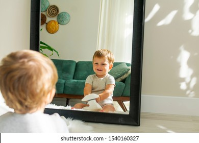 when you are bored at home.small funny baby boy  sitting next to big mirror and trying to wear properly sun hat of his father.