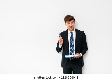 when you got an idea. elegant man in suit standing on white background and comming with a briliant idea, holding a clipboard in hands
