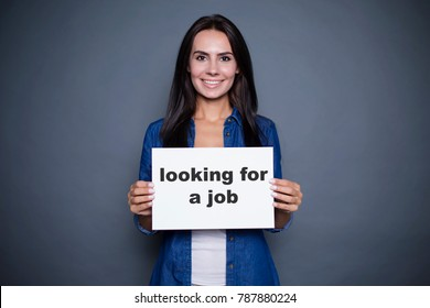 "Where is my job? Beautiful modern smiling woman in a jeans shirt is holding a sign with the inscription ""looking for job"" on a gray background isolated."