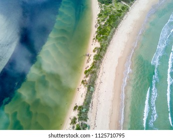 Where ocean meets river, separated by a narrow sand dune.  Aerial views  showing snd wave patterns and colours.