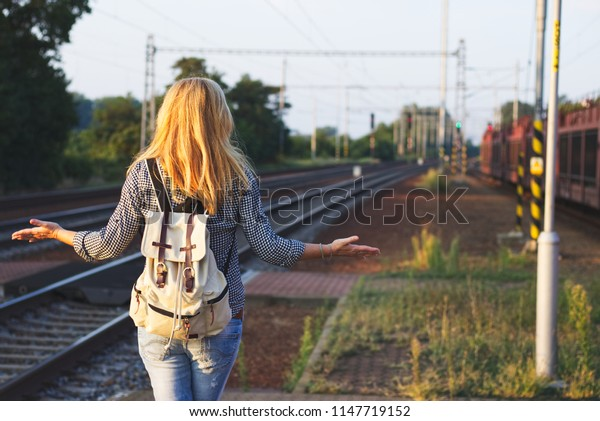 Where is the train? Woman waiting for train on railroad station. Backpacker travelling in Europe