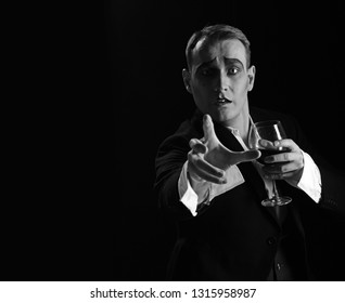 Where are you. Stage actor pantomime drinking wine. Comedian with mime makeup hold wine glass. Mime artist perform on stage. Drama theatre actor miming. Theatrical performance art and silen comedy.