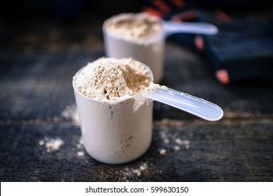 Whey powder in measuring scoops on wooden background.