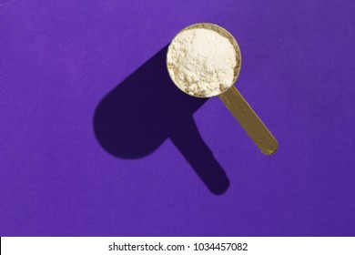 Whey protein food supplement for training and exercise. Minimal concept and hard light. Scoop with vanilla flavoured powder on violet background.