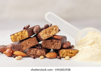 Whey protein powder in measuring scoop, nuts and different energy protein bar on grey background.
